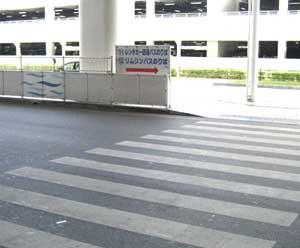 横断歩道を渡ると、レンタカー送迎バス乗り場の看板がございます。